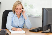 Cute blonde businesswoman on mobile writing something down — Stock Photo