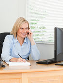 Cute businesswoman on mobile writing something down looks at her — Stock Photo