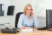 Cute businesswoman on mobile noting something looks into camera — Stock Photo