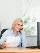 Businesswoman smiling at screen while phoning and holding a pape — Stock Photo