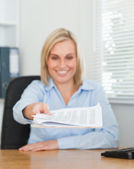 Smiling blonde businesswoman passing a paper looking at it — Stock Photo
