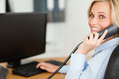 Young blonde businesswoman smiling into camera while on the phon — Foto de Stock
