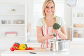 Woman cooking broccoli looks into the camera — Stock Photo