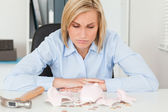 Sulking woman sitting in front of an shattered piggy bank with l — Stock Photo