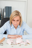 Sulking woman sitting in front of an shattered piggy bank — Stock Photo