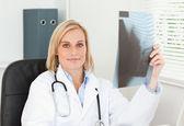 Uroczy lekarz trzymając rtg wygląda na aparat — Zdjęcie stockowe