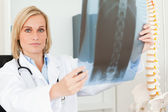 Serious doctor looking at x-ray looks into camera — Stockfoto