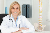 Smiling doctor with model spine next to her — Stock fotografie