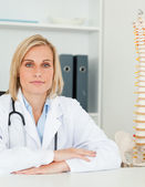 Serious doctor with model spine next to her looks into camera — Stok fotoğraf