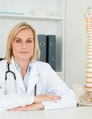 Un médecin sérieux avec colonne vertébrale modèle à côté d'elle se penche sur la caméra — Photo