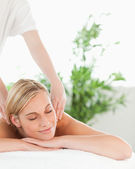 Close up of a blonde woman relaxing on a lounger enjoys a massage — Stock Photo