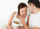 Woman fed with cereal by her man — Stok fotoğraf
