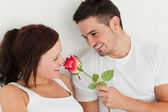 Portait of man and woman in a bed with a rose — Stock Photo