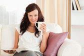 Relaxed woman sitting on a sofa with coffee and magazine — Stock Photo