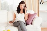 女人在电话上与她的大腿上的一本杂志 — 图库照片