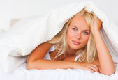 Blonde woman under a duvet — Stock Photo