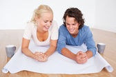 Close up of a couple looking at a plan with cups of coffee — Stock Photo