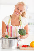 Portrait of a cute woman putting cabbage on water — Stock Photo