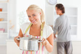 Woman posing with a boiler while her fiance is washing the dishe — Stock Photo