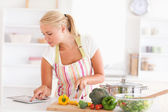 Blonde frau mit einem tablet pc zu kochen — Stockfoto