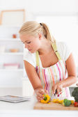 Portrait of a blonde woman using a tablet computer to cook — Stock Photo