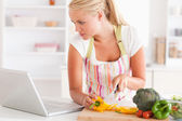 Close up of a woman using a laptop to cook — Stock Photo