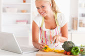 Close up of a blonde woman using a laptop to cook — Stock Photo