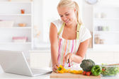 Close up of a blonde woman using a notebook slicing a pepper — Stock Photo