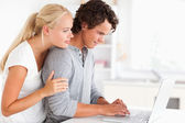 Lovely couple using a notebook — Stock Photo