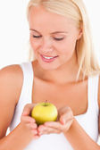Glorious blond woman holding an apple — Stock Photo