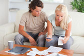 Shocked couple calculating their expenses — Stock Photo