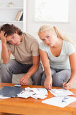 Despaired stressed couple calculating their expenses — Stock Photo