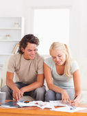 Happy couple calculating their expenses — Stock Photo