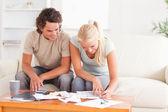 微笑对夫妇计算他们的费用 — 图库照片