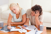 Unhappy couple listing expenses — Stock Photo