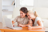 Cute couple with a laptop and a credit card — Stock Photo