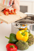 Vegetables being pushed into cooking pot — Stock Photo