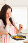 Woman looking at frying pan — Stock Photo