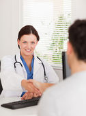 A female doctor is shaking hands with patient — Stock Photo