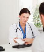 Kind female doctor giving patient prescription — Stock Photo