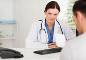 Female doctor with patient and prescription — Stock Photo