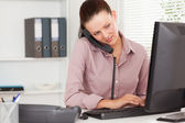 Businesswoman telephoning and typing — Stock Photo