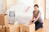 Female preparing cardboard box for transport — Stock Photo