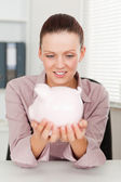 Businesswoman holding piggy bank at workplace — Stock Photo