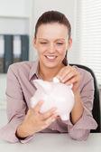Businesswoman putting money in piggy bank — Stock Photo