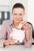 A businesswoman inserting money in piggy bank — Stock Photo