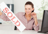 Businesswoman shows sold sign — Stock Photo