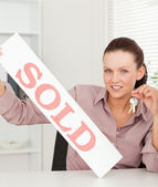 Businesswoman holding keys and sold sign — Stock Photo