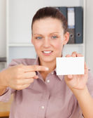 Gorgeous businesswoman pointing at a card — Stock Photo