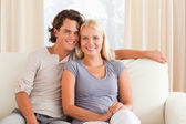 Smiling couple sitting on a sofa — Stockfoto